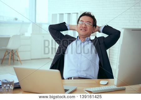 Cheerful mature businessman resting at his workplace