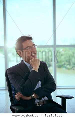 Cheerful Asian businessman pondering over new idea