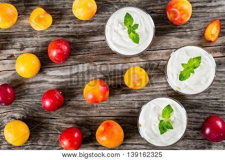 fresh greek yogurt with cherry plums decorated with mint leaves in cups ripe plums on wooden background view from above
