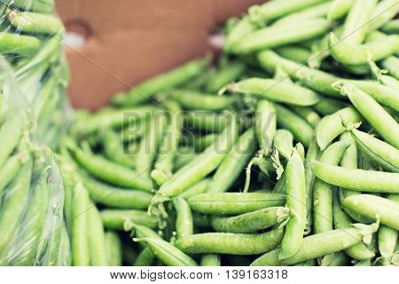 sale, harvest, food, vegetables and agriculture concept - close up of green peas in box at street market
