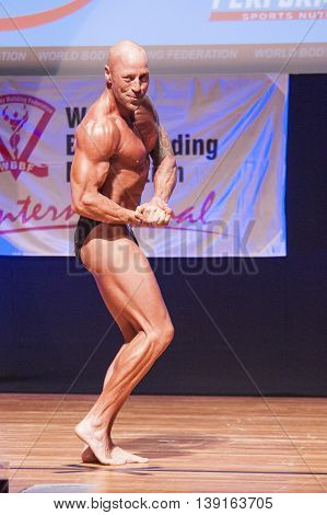 MAASTRICHT THE NETHERLANDS - OCTOBER 25 2015: Male bodybuilder Erik Stobbe flexes his muscles and shows his best physique in a chest pose on stage at the World Grandprix Bodybuilding and Fitness of the WBBF-WFF