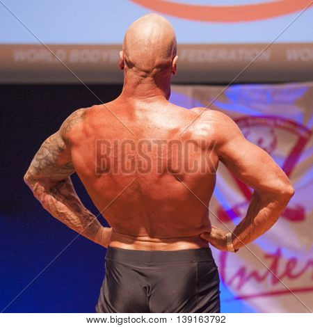 MAASTRICHT THE NETHERLANDS - OCTOBER 25 2015: Male bodybuilder Erik Stobbe shows his best lats spread pose at the World Grandprix Bodybuilding and Fitness of the WBBF-WFF on October 25 2015 at the MECC Theatre in Maastricht the Netherlands.