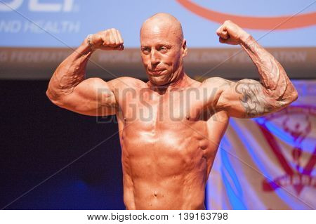 MAASTRICHT THE NETHERLANDS - OCTOBER 25 2015: Male bodybuilder Erik Stobbe shows his best front double biceps pose at the World Grandprix Bodybuilding and Fitness of the WBBF-WFF on October 25 2015 at the MECC Theatre in Maastricht the Netherlands.