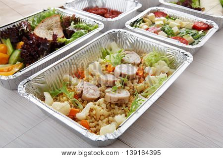 Healthy food delivery and diet concept. Take away of fitness meal. Weight loss nutrition in foil boxes. Bulgur pilaf with fish rolls and boiled cauliflowers and other dishes at white wood