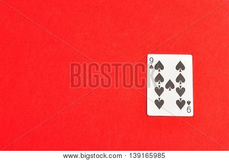 Playing card. Nine of spades isolated on a red background