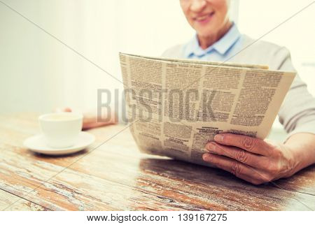 age, leisure and people concept - close up of happy senior woman drinking coffee and reading newspaper at home