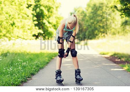 fitness, sport, summer, rollerskating and healthy lifestyle concept - happy young woman in rollerskates and protective gear riding outdoors
