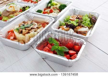Berry dessert and other dishes restaurant delivery. Sweet strawberry salad in foil box at white wood. Healthy food take away