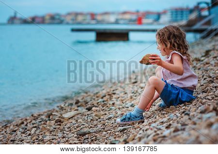 adorable dreamy child girl relaxing on the beach in Piran Slovenia