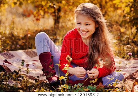 happy kid girl in red sweater having fun on autumn picnic sitting on cozy blanket