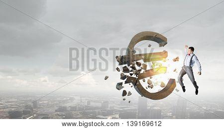 Man attacking euro symbol . Mixed media