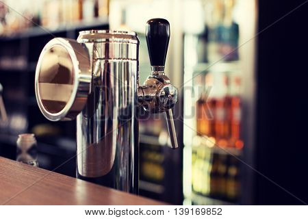 drink, equipment and object concept - close up of single tap chrome draft beer kegerator tower at bar or pub