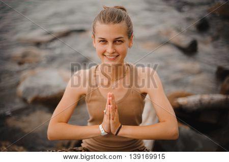 beautiful smilng woman performing namaste gesture on beach