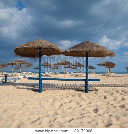 Different parasols and sun loungers on the empty beach on Tavira island Algarve. Portugal