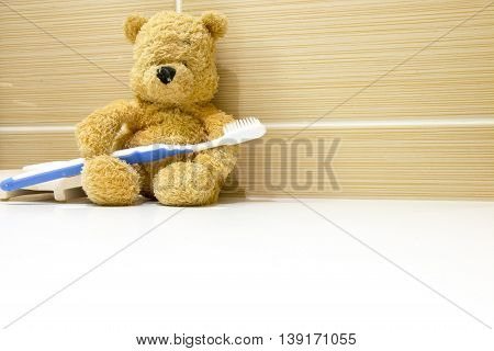 Bear is holding toothbrush for brushing in the morning