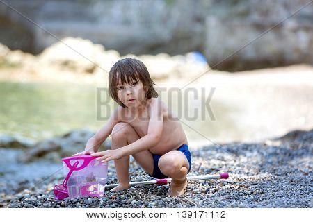 Cute Boy With Net For Fishing And Bucket, Trying To Catch Some Little Fishes In The Sea