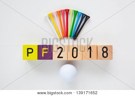 P.F.2018 - an inscription from children's wooden blocks and golf ball and wooden tees - Flat Lay Photography