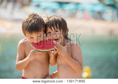 Two Little Children, Boy Brothers, Eating Watermelon On The Beach