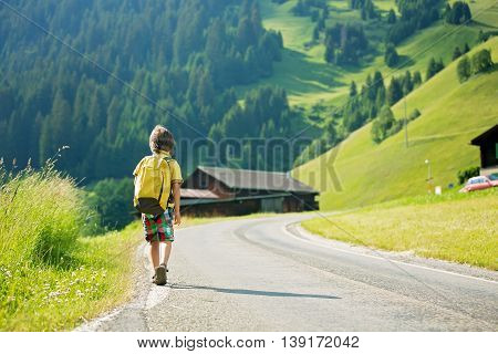 Cute Little Child With Backpacks Travel On The Road To Scenic Mountains