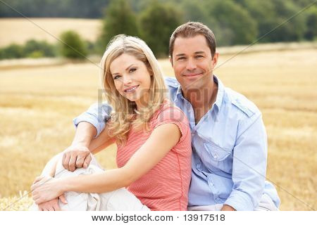 Couple Sitting On Straw Bales In Harvested Field
