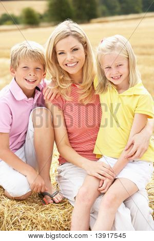 Mother And Children Sitting On Straw Bales In Harvested Field