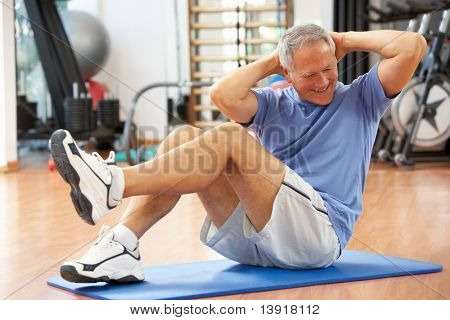 Senior Man Doing Sit Ups In Gym
