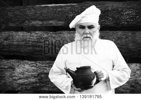 bearded man cook chef in uniform and hat with long beard on serious face holding iron old tea kettle sunny day outdoor on wooden background black and white
