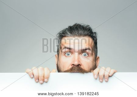 young man with surprised face with long hair behind white paper sheet in studio on grey background copy space