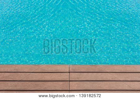 Close focus of edge of artificial wood floor near swimming pool with moving blue water as blurry background