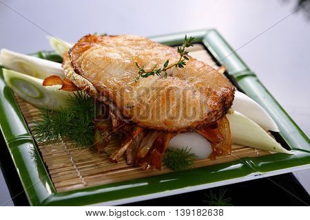 Fried loin of cod with onion on bamboo tray in restaurant