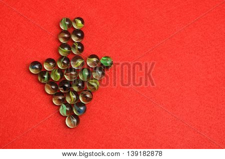 Marbles displayed in a arrow shape on red background