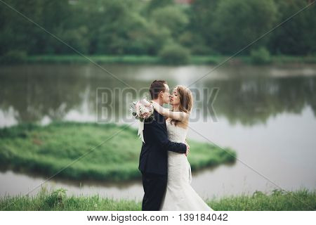 Beautifull wedding couple kissing and embracing near lake with island.