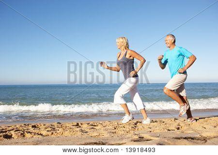 Постер, плакат: Старший пара в фитнес одежда идущую вдоль пляжа, холст на подрамнике