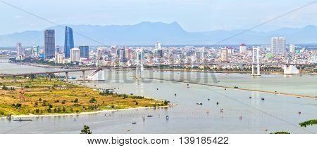 Da Nang, Vietnam - June 25th, 2015: Close Da Nang city with skyscrapers and beautiful architecture along Han River bridges on a beautiful bay, this the most tourist cities in Da Nang, Vietnam