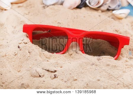Red Sun Glasses On Sand At Beach.