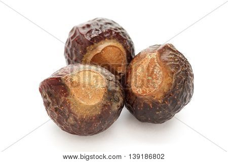 Organic Chinese soapberry or Reetha (Sapindus mukorossi) seeds. Isolated on white background. Macro close up. Top view.