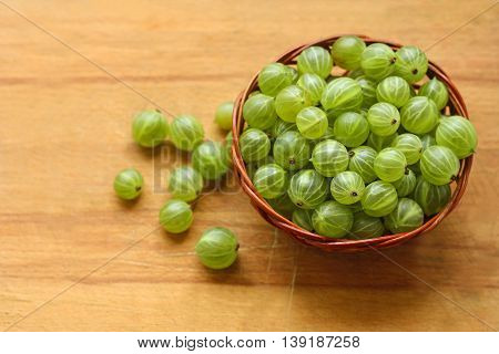 Berry background. Big ripe round green gooseberries in brown wicker small basket on old wooden scratched the surface.