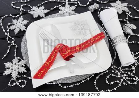 Modern christmas table setting with square porcelain plates, red ribbon, cutlery, napkin and ring with silver snowflake and bead chain decorations over dark wood background.