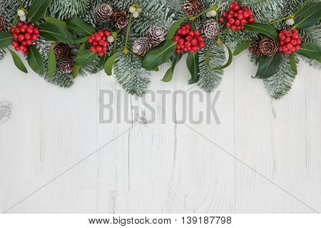 Traditional winter and christmas background border with flora of holly, mistletoe, fir leaf sprigs and pine cones over distressed white wood.