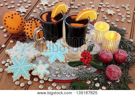 Christmas mulled wine, snowflake gingerbread biscuits, orange pomanders and frosted apple decorations, with candles, holly and winter greenery over oak background.