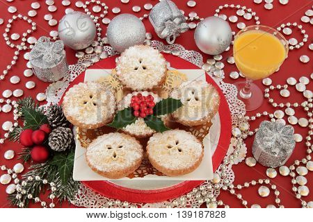 Christmas mince pie cakes with egg nog drink, silver bauble decorations, holly and winter greenery on red background.