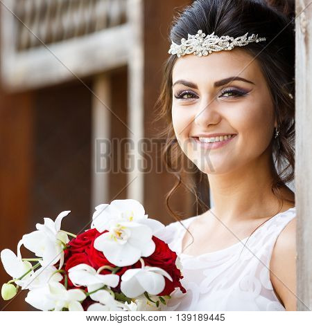 Beautiful bride with bouquet against the wooden background