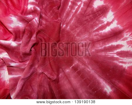 red fabric with white abstract pattern laid in the crease