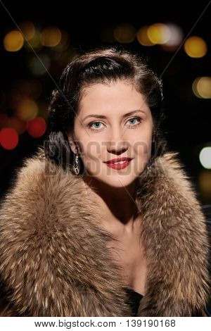 woman studio portrait in hollywood style light with night lights background