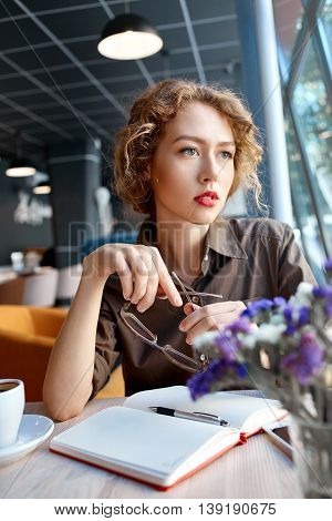 joyful reflective woman sitting in a cafe with notebook at a table made of wood . in the background a bright window with bright daylight