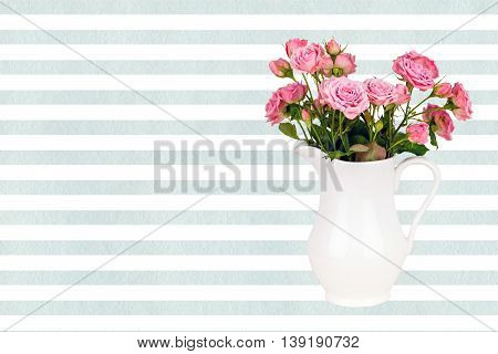 Pink flowers in white jug on watercolor blue stripes background. Roses in jug on LightCyan watercolor striped background. Background with flowers. Background with pink roses.