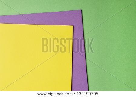 Colored cardboards background in yellow purple green tone. Copy space. Horizontal