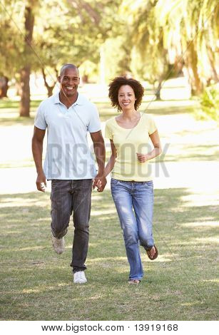 Portrait Of Young Couple Running Through Park