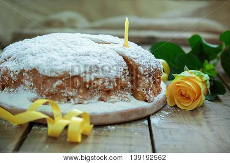 Birthday party. Birthday in yellow style. Home cake. Piece of cake with a candle on a wooden table yellow rose and ribbon