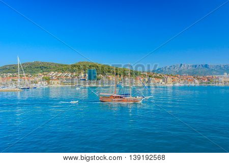 Touristic route with wooden boat with city of Split in background, summertime in Croatia.